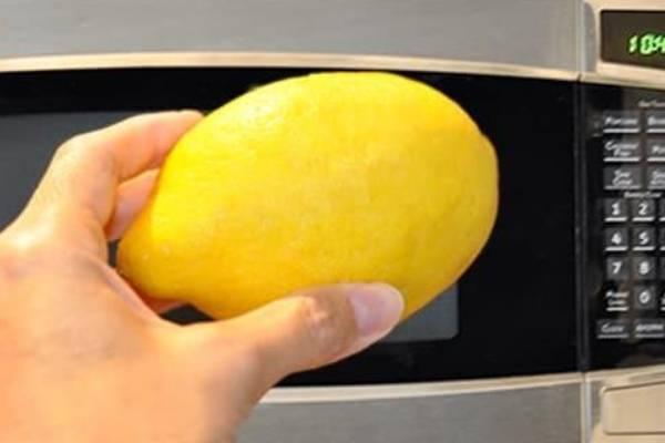 Holding Lemon Near Microwave