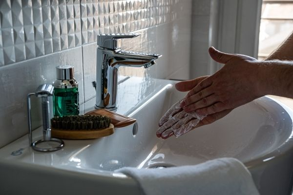 Earth Day- A person scrubbing soap on their hands with the water tap off
