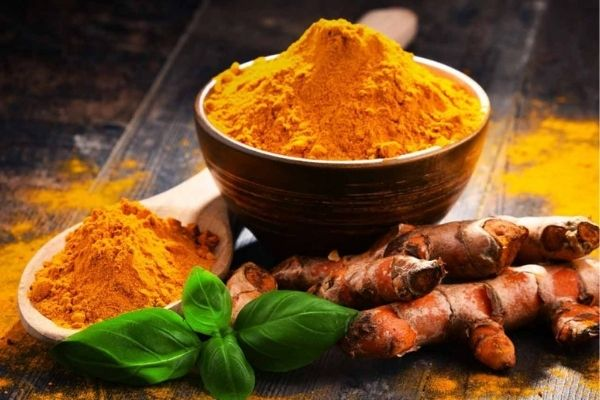 The superfood turmeric in a bowl along with some turmeric roots as well