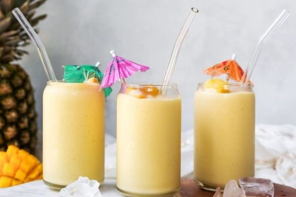Mango Drink Recipes: Three glasses of mango colada with a pineapple and mango in the background