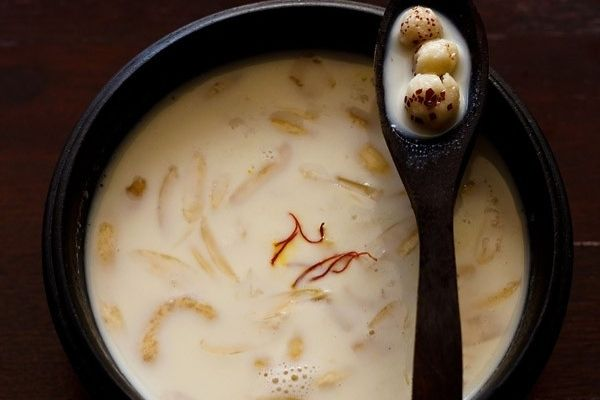Makhana kheer in a black bowl with some makhanas in a spoon