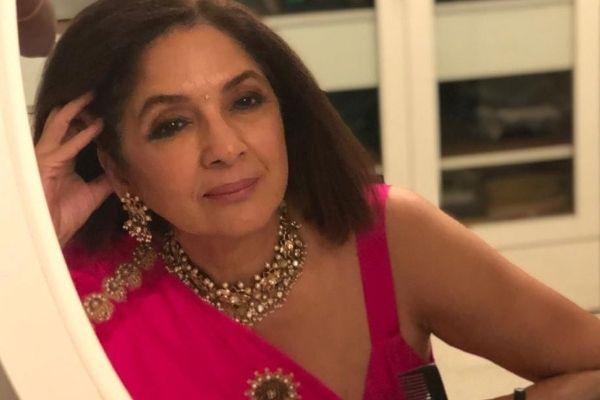 The stunning Neena Gupta in a pink saree, looking into the mirror