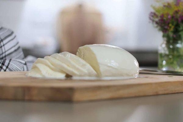 Semi-Soft Cheese: A sliced block of Mozzarella cheese kept on a chopping board