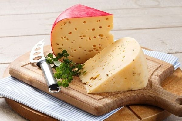 Semi-Firm Cheese: A cut block of Gouda cheese kept on a chopping board with a cheese knife