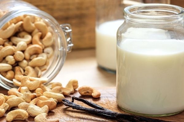 A glass jar with dairy-free cashew milk and cashews on the side