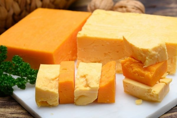 Firm Cheese: A few blocks of cheddar cheese kept along with some cut pieces