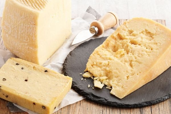 Hard Cheese: A variety of hard cheeses kept together on a wooden table