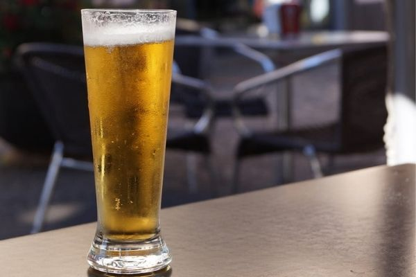 A beer glass kept on a table with two chairs in the background