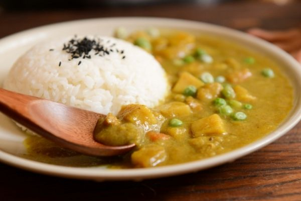 A portion of white rice served with some potatoes and peas curry on a cream coloured plate