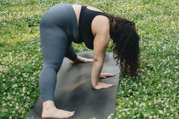 A woman stretching by bending over on a yoga mat